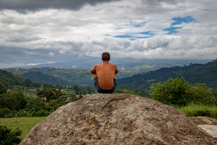 Rear View Of Shirtless Man Sitting At Mountain Against Sky