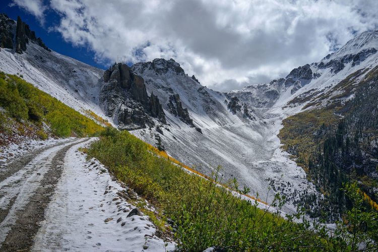 A snow road to mountain with clouds and blue sky with yellow leafs aspen in autumn, colorado.