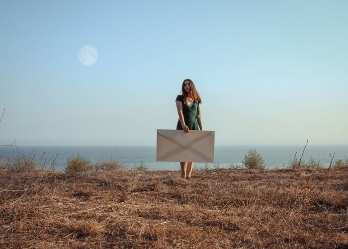 Woman holding large envelope while standing on field against sea and clear sky