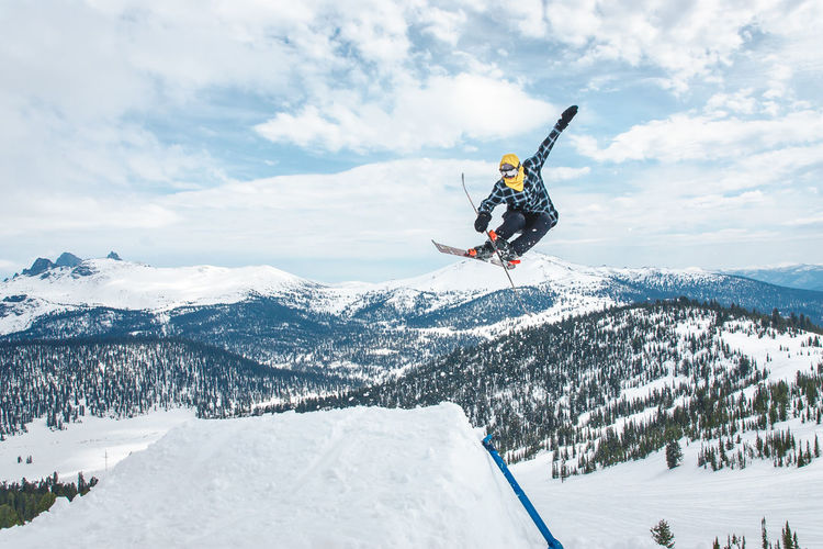 Full Length Of Person Jumping While Skiing At Snow Covered Mountains Against Sky