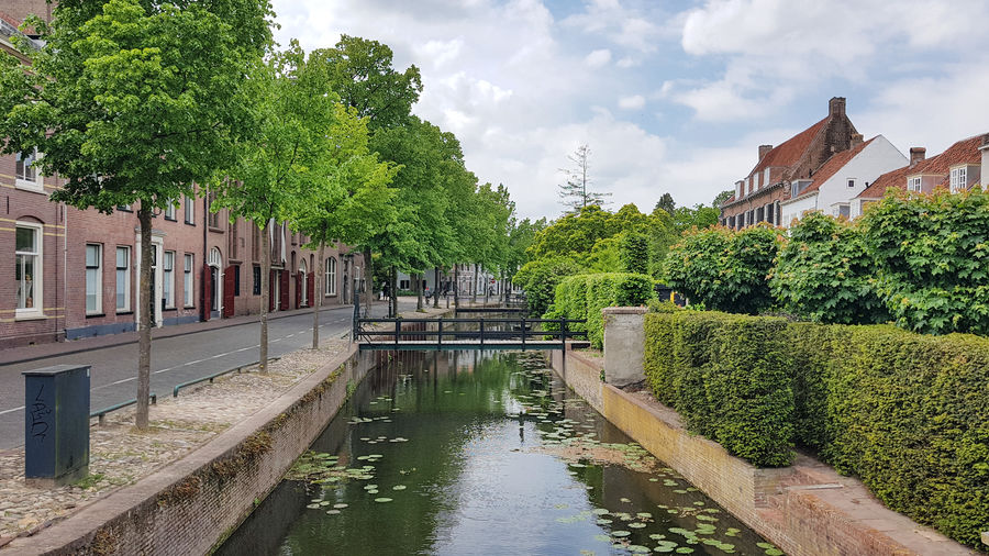 Bridge over canal amidst trees and buildings against sky