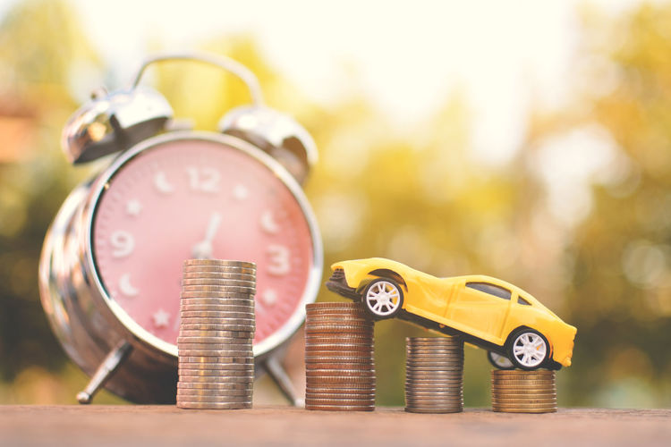 Close-up of alarm clock with stacked coins and toy car on table