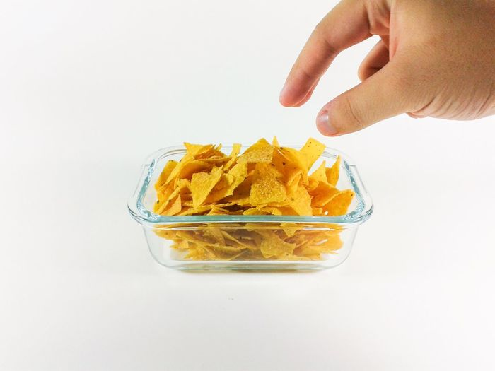 Cropped Hand Over Fresh Nacho Chips In Glass Bowl Against White Background