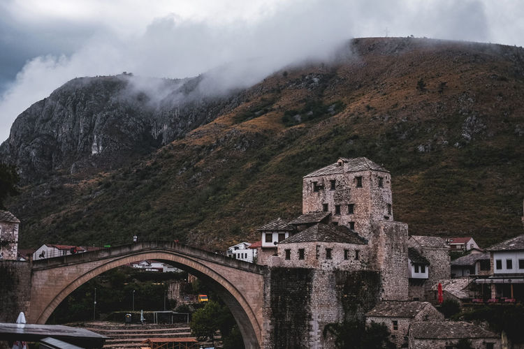 Arch bridge by buildings against sky