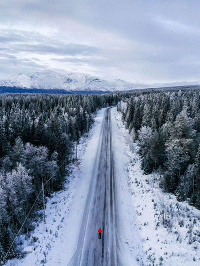High angle view of road amidst snow covered trees against sky