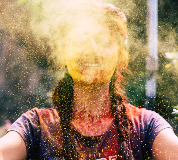 Young woman playing with powder paint during holi