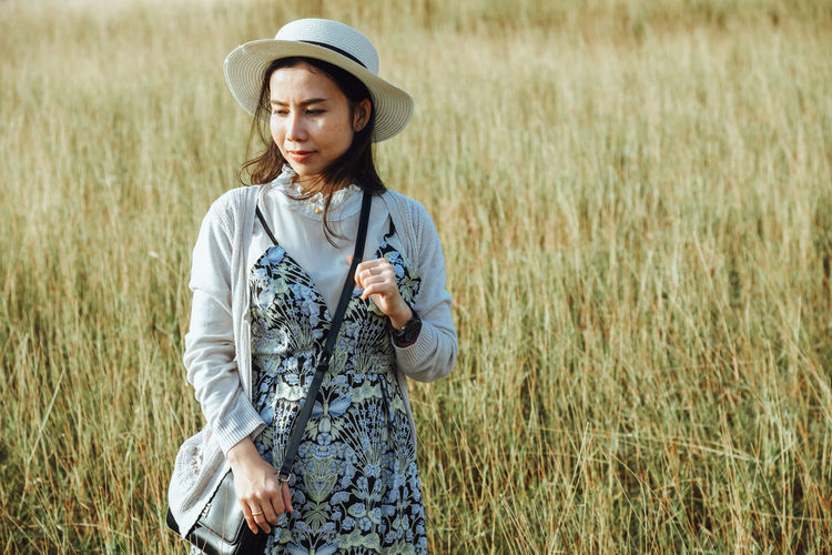 Thoughtful mid adult woman standing on grassy field