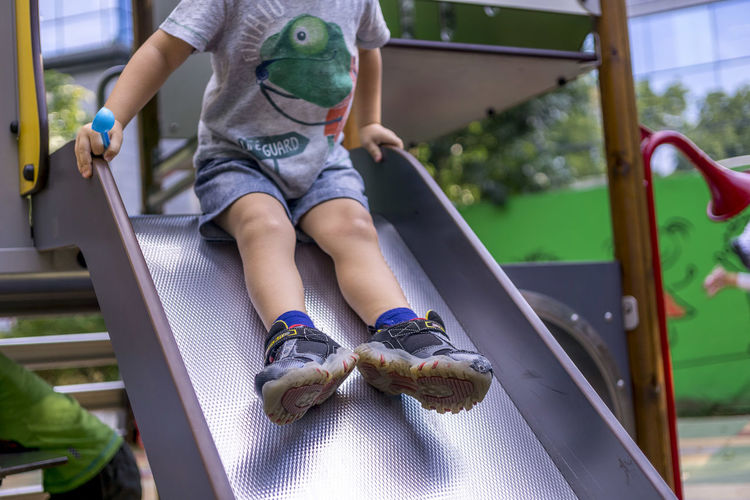 Low section of boy on slide at park