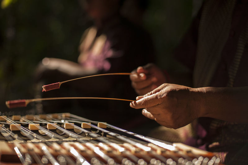 Midsection of musician playing xylophone