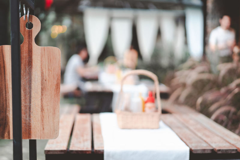 wooden cutting board ready yo use at restaurant with blurred customer and waiter, retro tone Abstract Atmosphere Autumn Backdrop Background Board Bokeh Couple Customer  Cutting Decorate Dinner Dry Flag Hang Lifestyle Light Pine Relationship Reserve Restaurant Retro Time Together Tone Waiter Wooden
