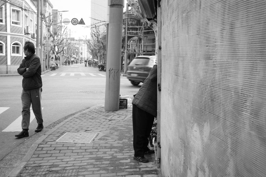 Architecture City Street Built Structure Building Exterior Footpath Full Length Real People Sidewalk Rear View One Person Day Men Car Walking Motor Vehicle Transportation City Life Incidental People Outdoors Alley Paving Stone Social Issues Blackandwhite Streetphotography
