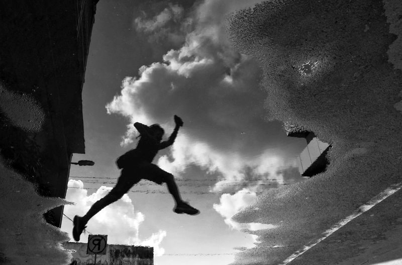 Retribution City Location Jumpshot Puddle Reflections Inverted Clouds In The Sky Street Photography Humor Decisive Moment Forced Perspective Silhouettes Of People Black And White Photo Extreme Sports Jumping Full Length Stunt Mid-air Skill  Agility Sport Athlete Silhouette Energetic Energy Sprinting