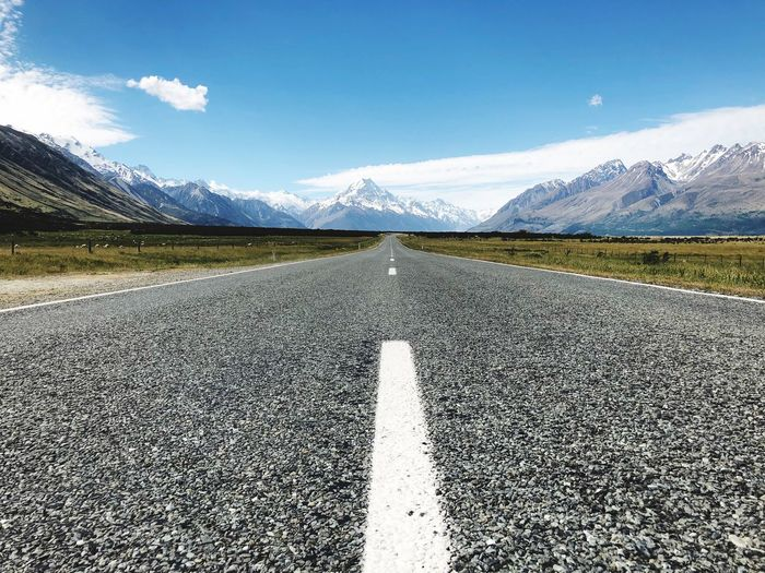 Surface level of road by mountains against sky