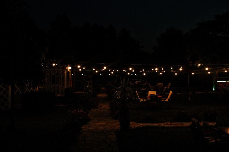 Silhouette people on illuminated street against sky at night