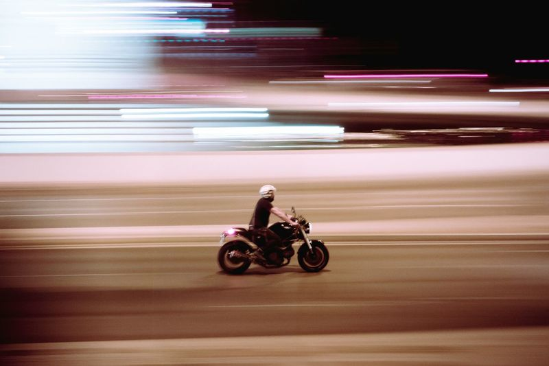 Blurred motion of man riding motorcycle on road at night