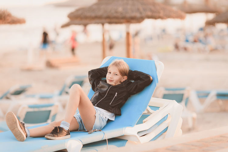 Full Length Portrait Of Smiling Girl Lying On Lounge Chair At Beach