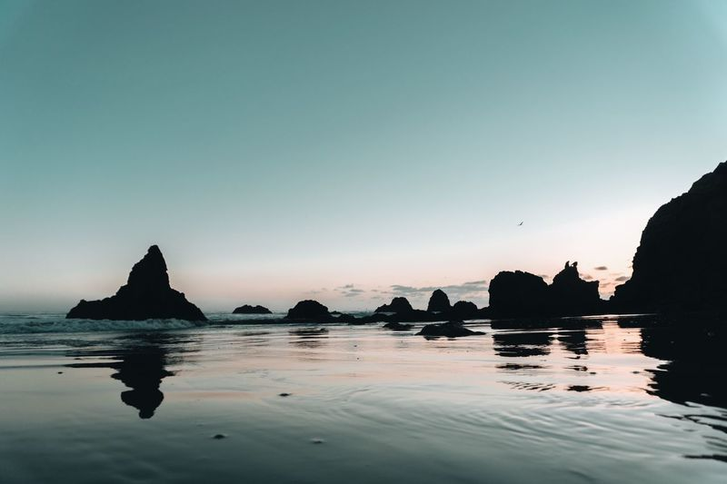 Silhouette rocks in sea against clear sky during sunset