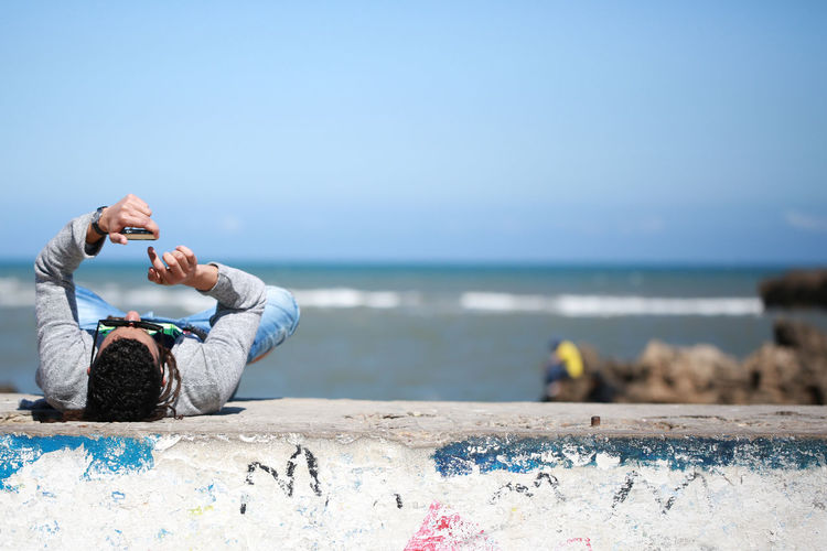 Mature man using smart phone while lying on retaining wall at beach against blue sky during sunny day