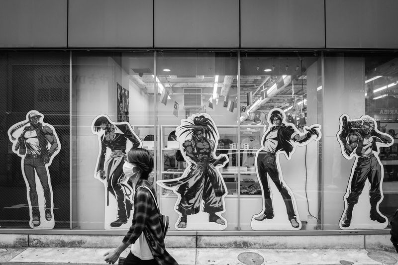 Walk On By Human Representation Glass - Material Representation Reflection Window Mannequin Female Likeness Indoors  Store Transparent Architecture Group Of People Illuminated People Real People Art And Craft Retail Display Male Likeness Fashion Character Cartoon Anime Walking Walking By Man Streetphotography Street Akihabara Japan Japan Photography Monochrome Blackandwhite Black And White EyeEm Best Shots EyeEmNewHere The Traveler - 2019 EyeEm Awards The Street Photographer - 2019 EyeEm Awards
