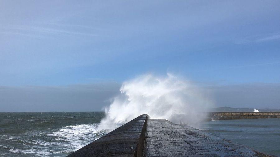 Sea waves splashing on pier against sky