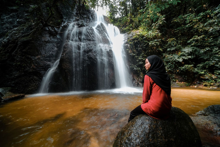 Rear view of girl sitting against waterfall in forest
