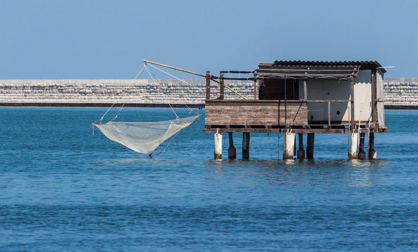 View Of Building On Sea With Fishing Net