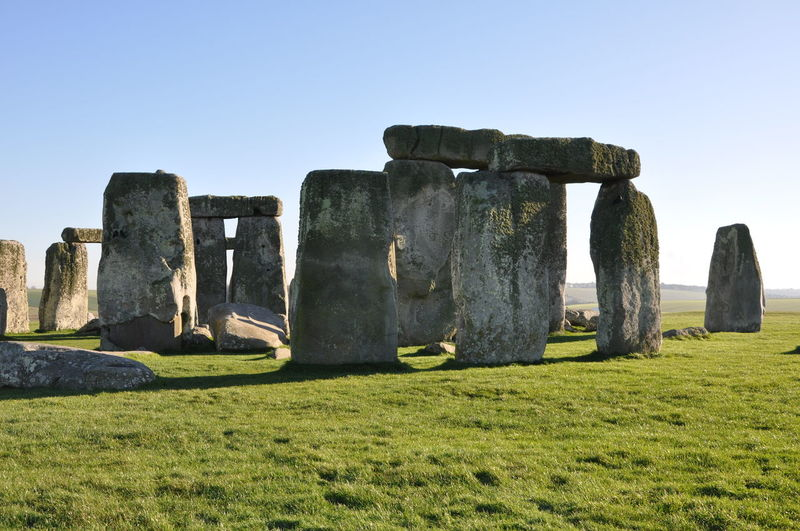 Historic stonehenge on grassy field against clear sky