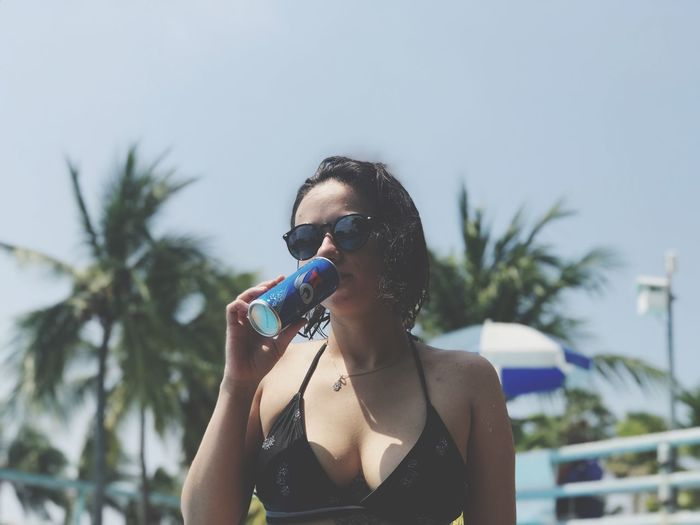 Portrait of woman drinking from can at poolside