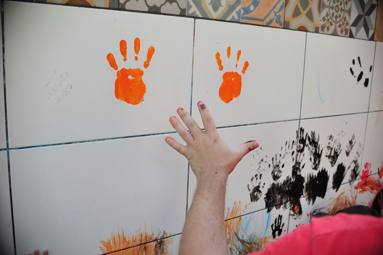 Cropped Image Of Man With Handprint On Tile Wall