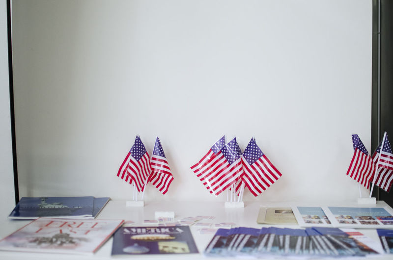 Flags on table against white wall