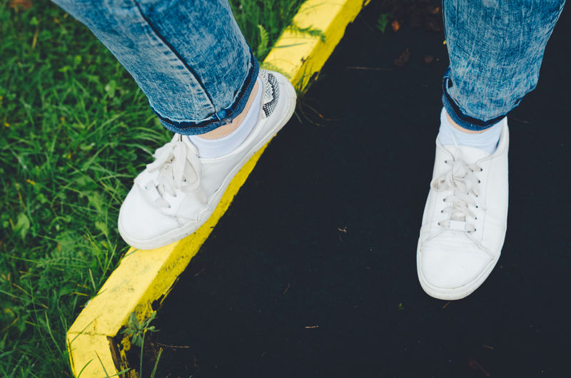 Low section of girl's white canvas shoes Blue Color Grass Green Color Jeans Textured  Backgrounds Body Part Canvas Shoe Casual Clothing Full Frame High Angle View Human Body Part Human Leg Jeans Leisure Activity Low Section Outdoors Real People Shoe Standing Summer Yellow Color