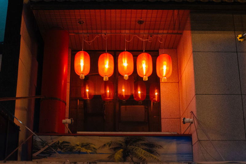 Illuminated lanterns hanging in building