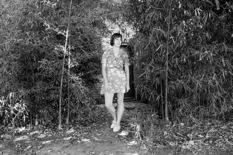 Woman standing by tree on field in forest