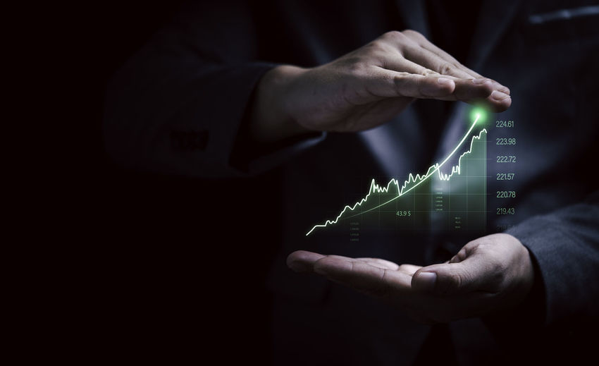 Businessman gesture protecting increasing virtual investment graph and chart for stock market