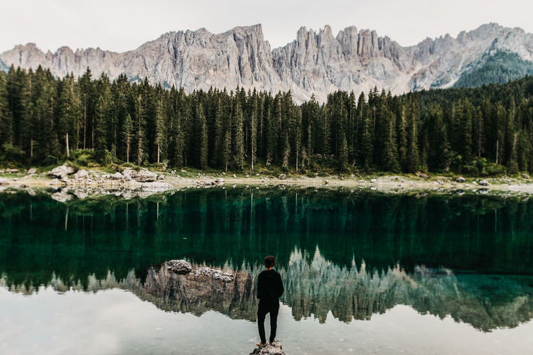 Girl is standing on a rock at lake Karersee Dolomites, Italy Lago Di Carezza Reflection Beauty In Nature Canon_photos Forest Girl Idyllic Karersee Lake Lake Mountain Mountain Range Nature One Person Outdoors Rear View Reflection Scenics - Nature South Tyrol Standing Tranquil Scene Tree Water A New Beginning