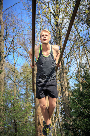 Low Angle View Of Man Exercising In Forest