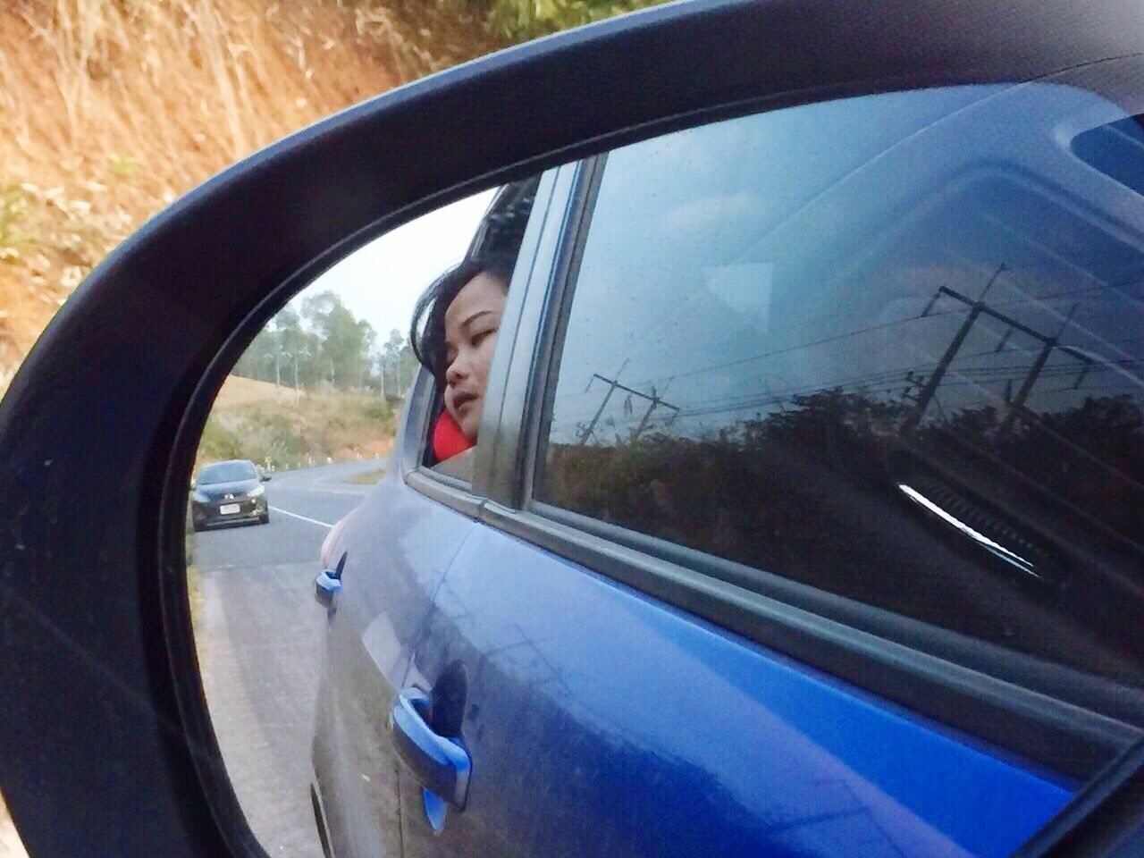 Reflection Of Woman Sitting In Car At Side-View Mirror