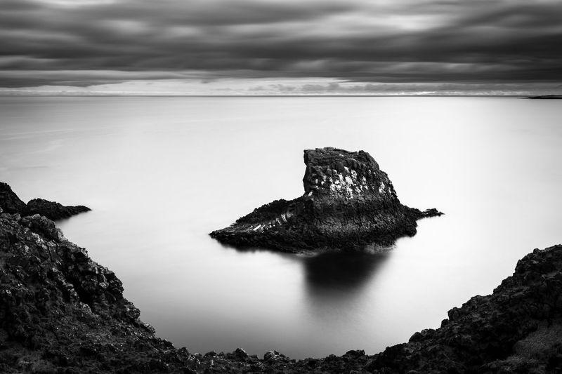 Rock on sea shore against sky