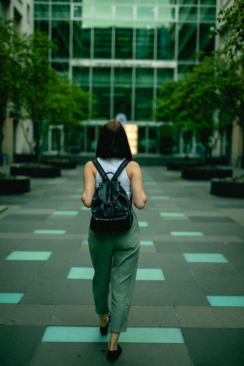Rear view of young woman walking towards modern building in city
