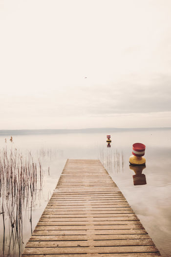 Beauty In Nature Calm Water Clear Sky Day Golden Hour Horizon Over Water Jetty Nature No People Outdoors Pier Ponton Reed Reflections In The Water Scenics Sea Sky The Way Forward Tranquil Scene Tranquility Water Wood Paneling