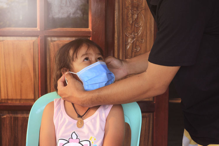 Father getting daughter dressed with face mask at home