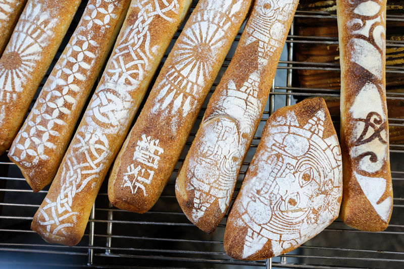 Directly above view of various baguette breads on metal grate at market