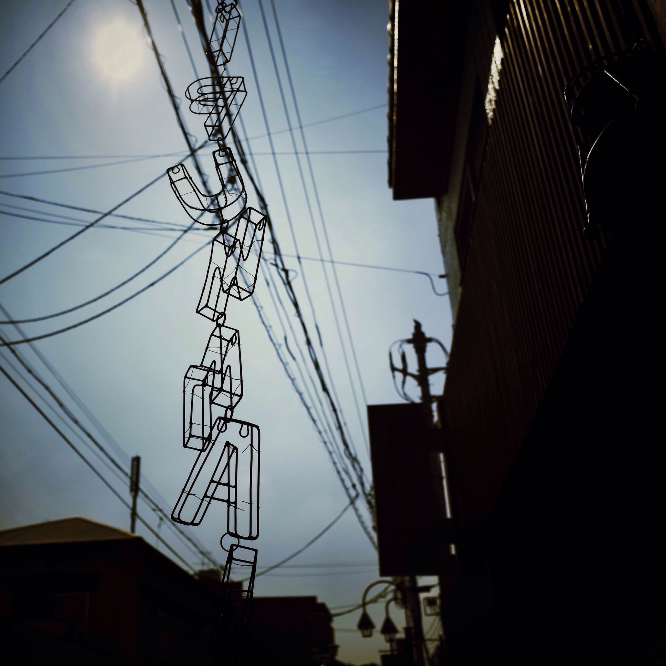 power line, electricity, electricity pylon, low angle view, power supply, cable, built structure, architecture, building exterior, silhouette, connection, fuel and power generation, sky, power cable, technology, house, dusk, no people, outdoors, building