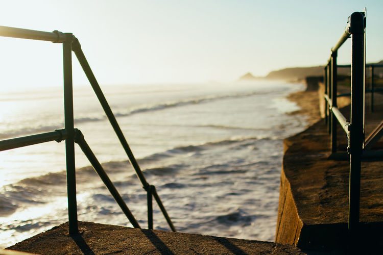 Close-up of railing by sea against sky