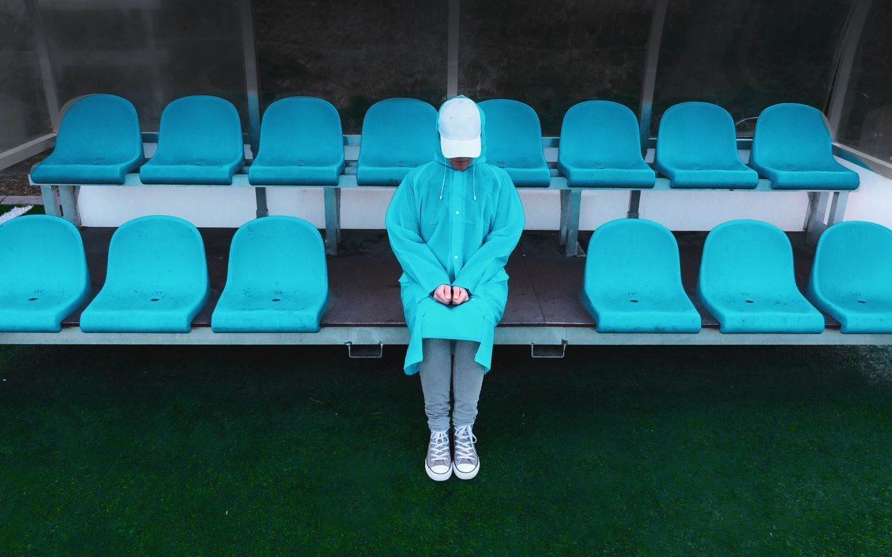 Woman in blue raincoat sitting on chair