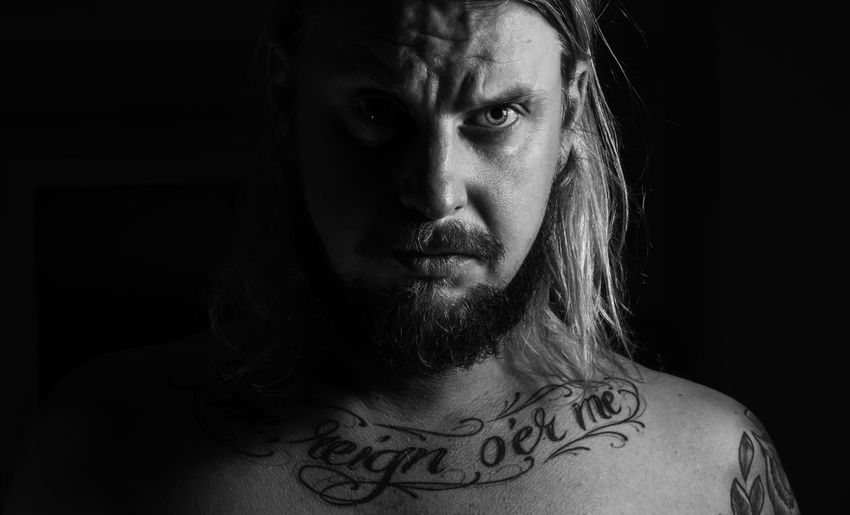 Close-Up Portrait Of Confident Shirtless Man Against Black Background