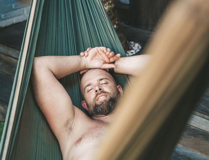 High angle view of man sleeping on hammock