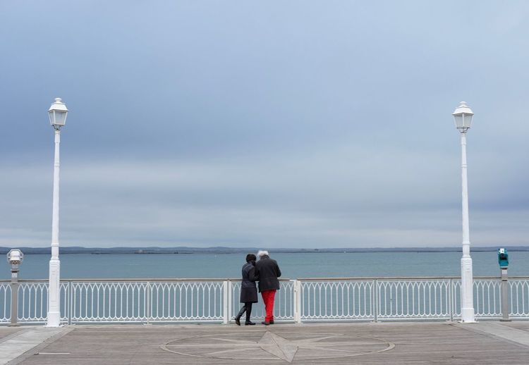 Rear view of couple standing at observation point against cloudy sky