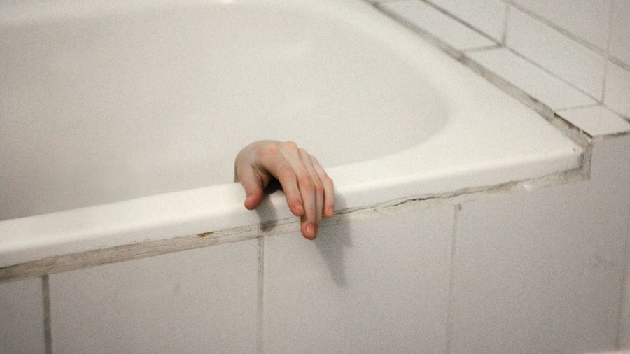 High Angle View Of Cropped Hand In Bathtub