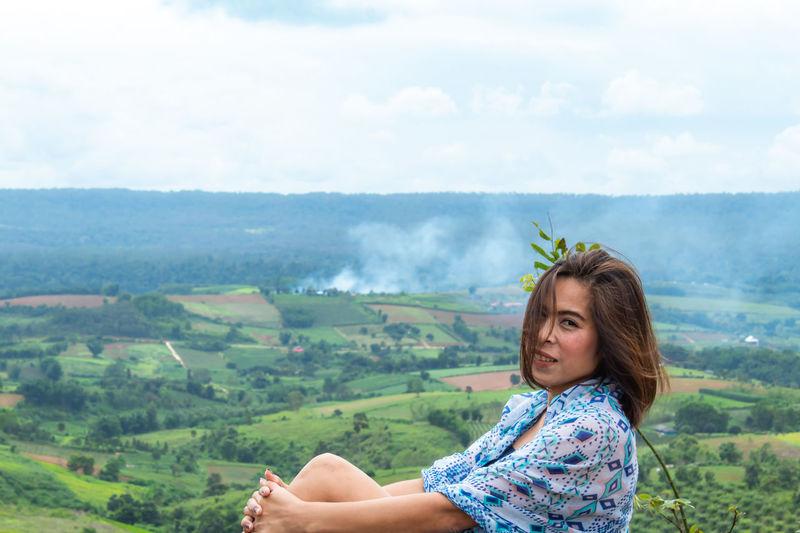 Portrait Of Woman Sitting Against Landscape